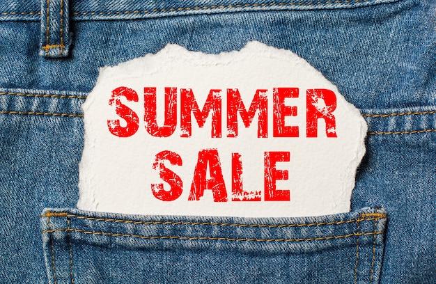 Liquidação de verão em papel branco no bolso da calça jeans azul