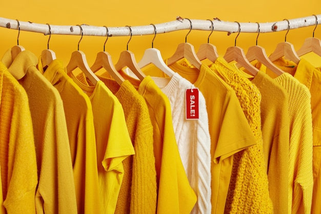 Liquidação total em loja de roupas. grandes descontos em suéteres. pulôver tricotado em rack com etiqueta.
