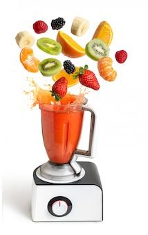 Liquidificador com frutas a voar em branco isolado
