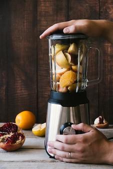Liquidificador com várias frutas no fundo de madeira