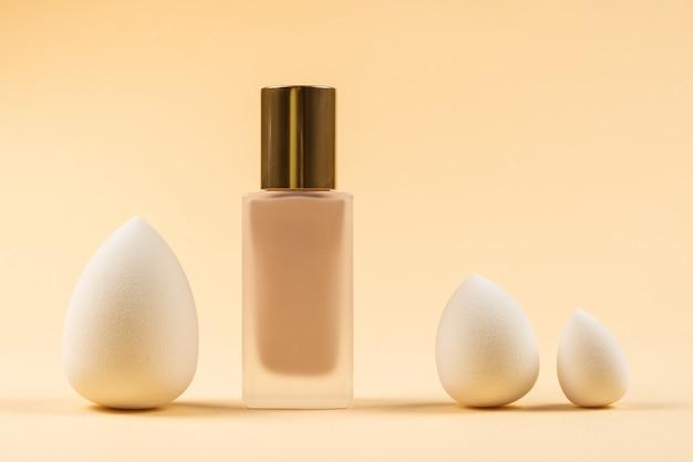 Liquidificador de beleza branca pequena, média e grande e base de maquiagem em fundo bege.