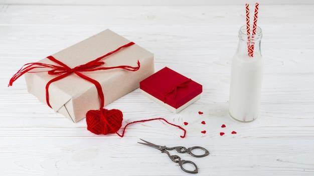 Líquido branco na garrafa com tubos perto de pequenos corações, tesoura e presentes