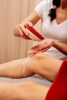 Líquido cosmético. trabalhador cuidadoso de cabelos compridos de salão profissional de spa adicionando creme branco nas pernas