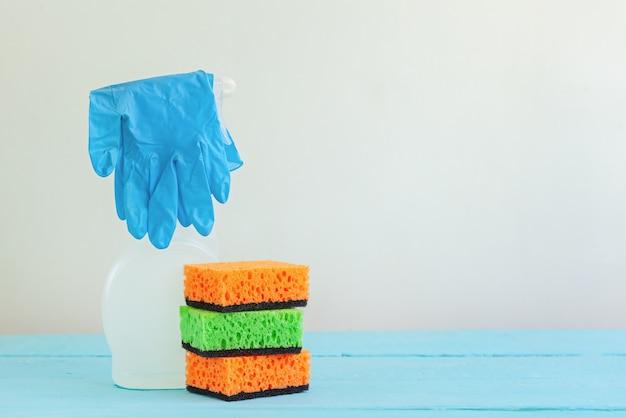 Líquido de limpeza de pulverizador branco da garrafa e esponja limpa em uma tabela.