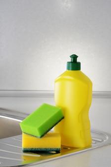 Líquido para lavar louça com uma esponja na pia da cozinha