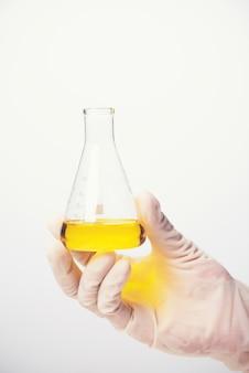Líquido químico nos produtos vidreiros do laboratório de ciência no fundo branco