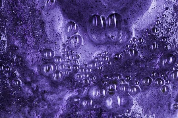 Líquido roxo fervente com espuma e gotas