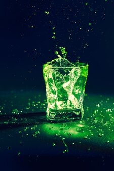 Líquido transparente de cor verde espirrando de vidro em azul escuro
