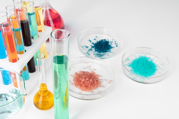 Líquidos coloridos dentro de vidraria na mesa branca em laboratório