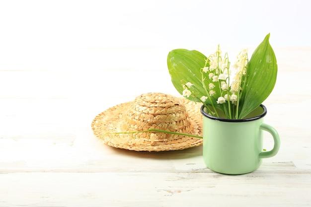 Lírios do vale em uma caneca esmaltada com um chapéu de palha em um fundo branco de madeira