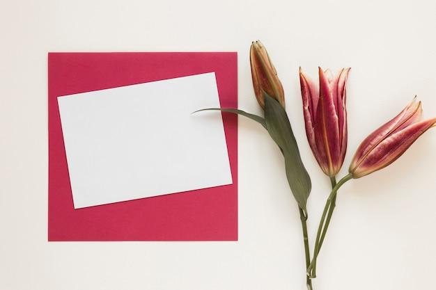 Lírios reais com envelope vermelho e pedaço de papel vazio Foto gratuita
