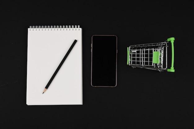 Lista de compras. caderno e lápis em um fundo preto. carrinho de compras com espaço de cópia