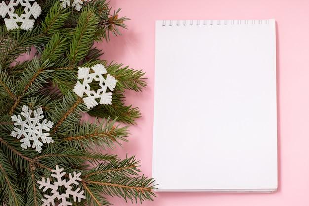 Lista de desejos de natal em rosa com ramos de abeto e flocos de neve, copyspace
