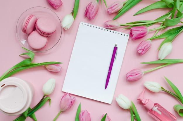 Lista de desejos do bloco de notas para planos futuros. composição plana leiga com fundo de flores, um bloco de notas, xícara de café e doces