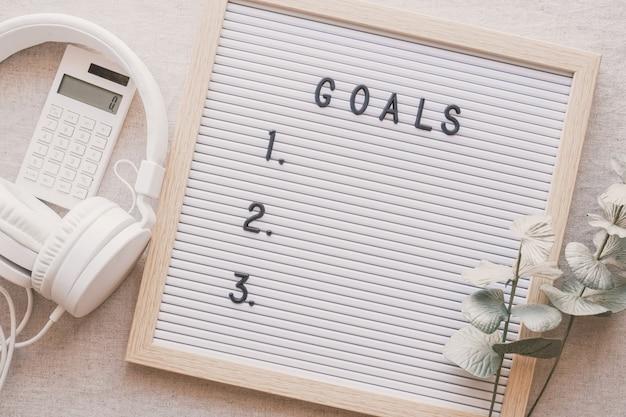 Lista de metas em quadro de avisos com fone de ouvido e calculadora resoluções de ano novo