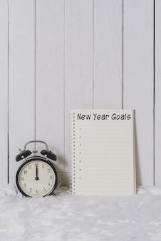 Lista de objetivos de ano novo, escrita no caderno com despertador
