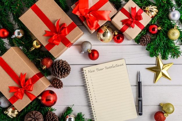 Lista de resoluções de ano novo escrita no caderno com abeto e decoração de natal
