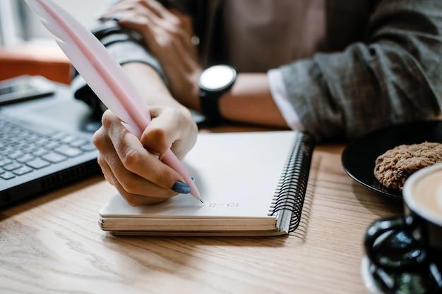 Lista de tarefas, organização de planos de projetos, lista de verificação produtividade trabalhos mulher escrevendo para lista de tarefas perto de