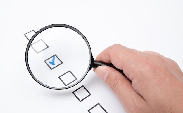Lista de verificação em papel branco com lupa
