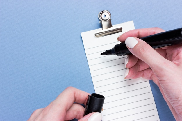 Lista de verificação importante do negócio, planejamento para lembrete de compra ou lista de tarefas prioritárias do projeto sobre fundo azul, com espaço de cópia. marcador nas mãos femininas