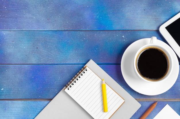 Lista de verificação, papel de nota vazio com o copo de café na madeira azul. escritório, escritor ou estudo conceito, vista superior, lay plana