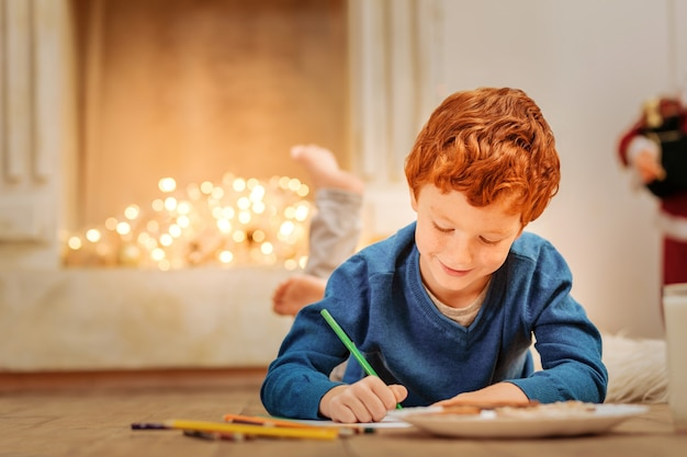 Listando presentes que eu gostaria de receber. adorável criança ruiva sorrindo enquanto estava deitada no chão e escrevendo uma carta para o pai do natal em casa.