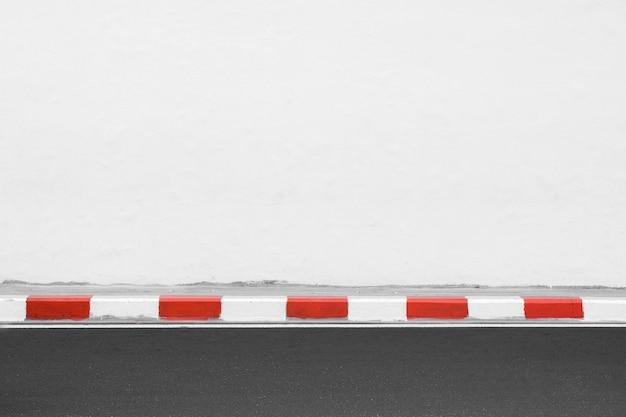 Listra branca e vermelha na beira da estrada de asfalto