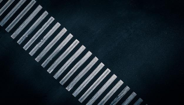 Listras brancas de tinta na designação de faixa de pedestres vazia de uma faixa de pedestres em um pe ...