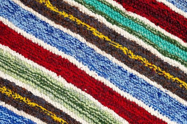 Listras coloridas diferentes na superfície do tecido de malha. close-up de tapetes retrô de têxteis ou tapetes. a textura do tecido é uma combinação com a geometria das linhas. produto artesanal