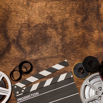 Listras de filme; bobina de filme e claquete na mesa de madeira