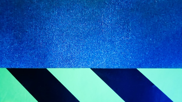 Listras diagonais amarelas e pretas em uma parede azul problemática. padrão minimalista colorido abstrato. fita adesiva de aviso de aviso sobre fundo azul.