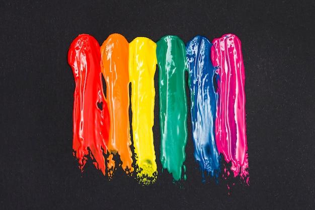 Listras multicoloridas de tinta a óleo no fundo preto