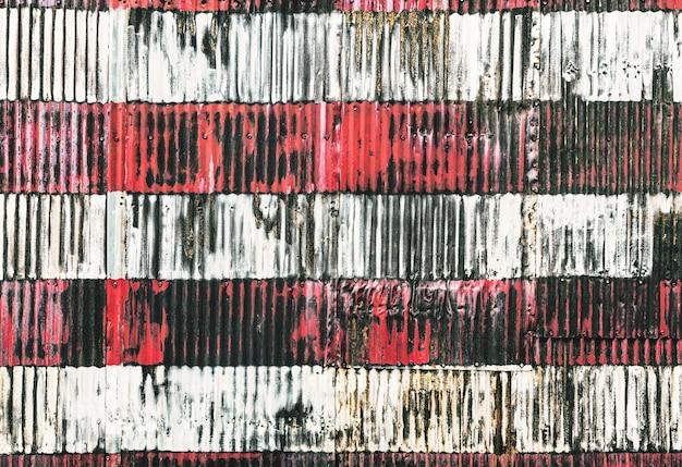 Listras vermelhas e brancas pintadas à mão em uma cerca enferrujada