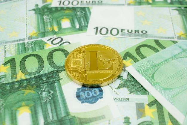 Litecoin moeda criptomoeda em notas de 100 euros close-up. criptomoeda golden ltc.