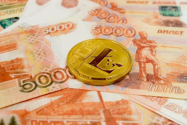 Litecoin moeda criptomoeda em notas de 5000 rublos russos close-up. criptomoeda golden ltc.