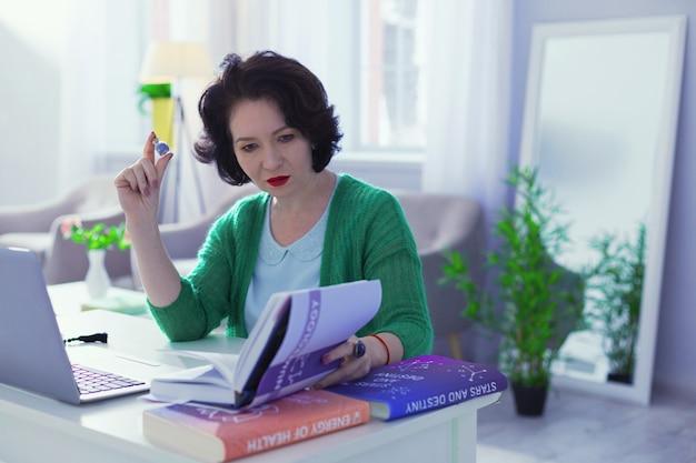 Literatura especial. bela mulher séria olhando para o livro enquanto quer checar algumas informações