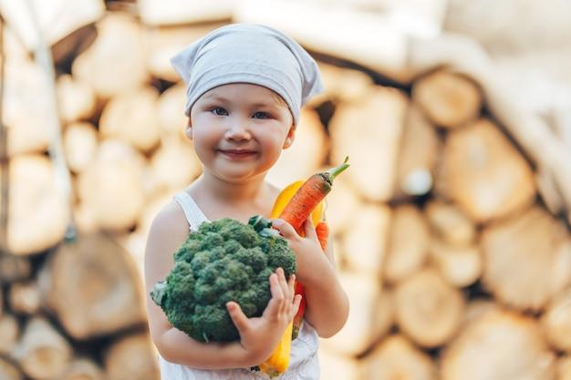 Litle feliz sorridente fazendeiro menino de macacão branco e bandana cinza segurando legumes orgânicos frescos nas mãos