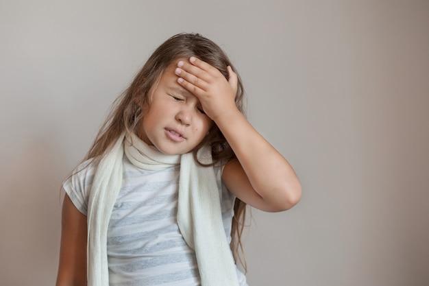 Litlle girl sentindo dor de cabeça com lenço branco em cinza.