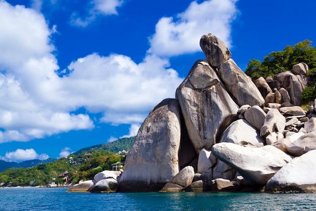 Litoral apedrejado da ilha contra o céu azul com nuvens. koh tao é