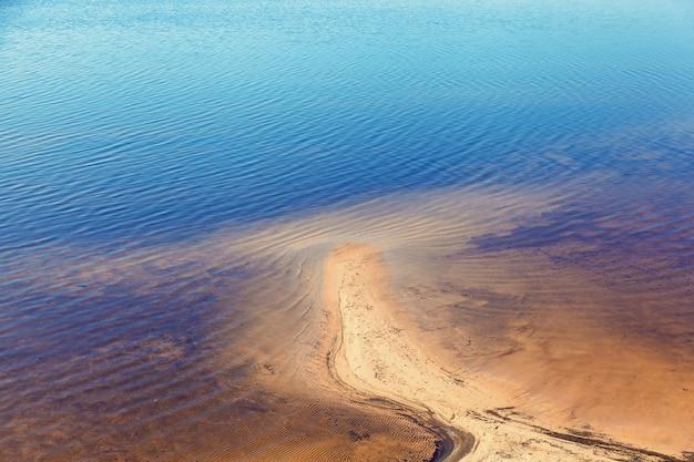 Litoral arenoso e bancos de areia na água.