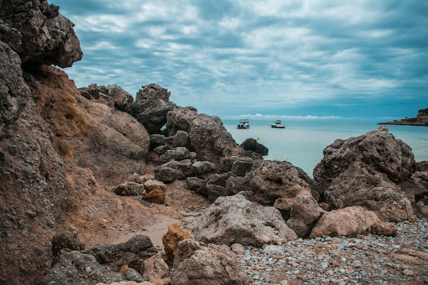 Litoral cheio de pedras, alguns navios no mar e o céu nublado