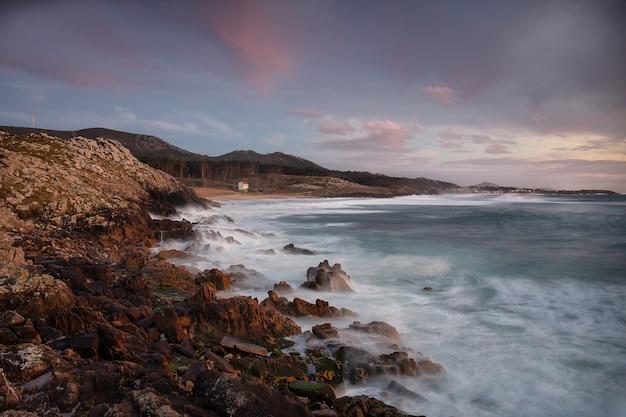 Litoral com pedras na costa durante o pôr do sol