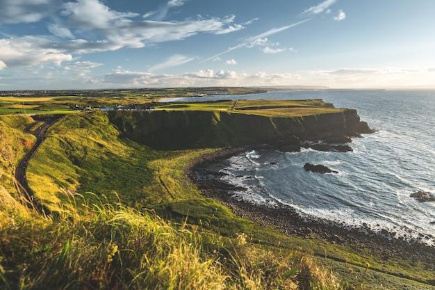 Litoral iluminado pelo sol. paisagem da irlanda do norte.