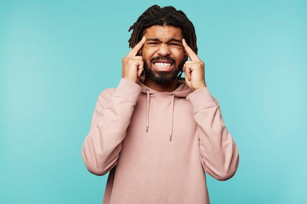 Litoral interno de um jovem homem de cabelos escuros de olhos castanhos com dreadlocks franzindo a testa e levando as mãos à cabeça enquanto sofre de dor de cabeça, isolado sobre um fundo azul