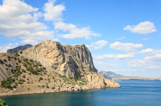 Litoral rochoso com pinheiros no fundo do céu azul e do mar (reserva