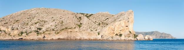 Litoral rochoso de verão e base militar no topo da rocha (cabo de alchak; arredores da cidade de sudak, crimeia, ucrânia). três tiros costuram a imagem.