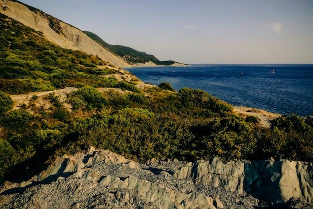 Litoral rochoso montanhoso coberto com floresta de zimbro no verão.