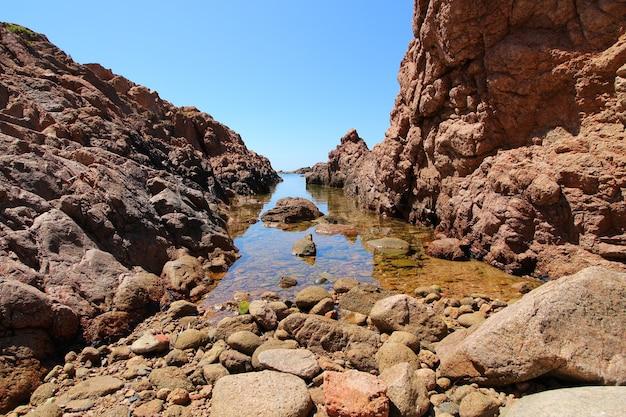 Litoral rodeado de rochas e o mar ao sol