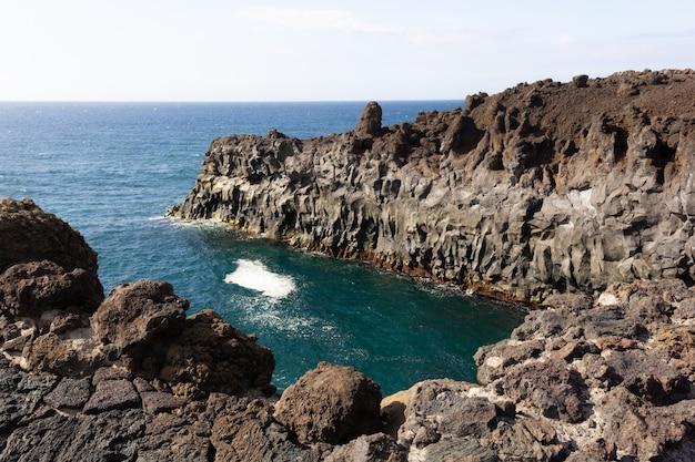 Litoral vulcânico à beira-mar na atração turística de los hervideros na ilha de lanzarote