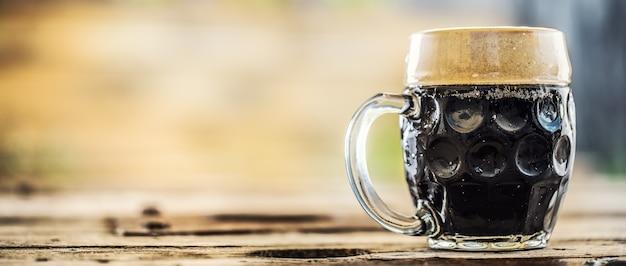 Litro de cerveja escura em uma mesa de madeira colocada ao lado de uma fotografia.